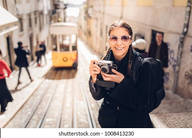 Smiling young traveler woman in Lisbon, exploring Portugal.Having fun on Europe trip.Tourist in front of famous 28 tram.Photographer blogger discovering european cities