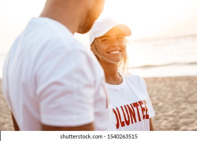Smiling young volunteer couple standing at the beach, talking