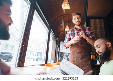 Smiling young waiter in brown apron taking an order from clients in cafe