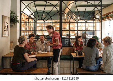 Smiling young waiter taking orders from a diverse group of customers sitting together at a restaurant table