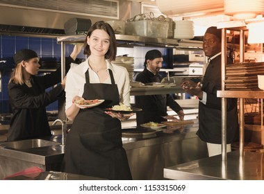 Smiling young waitress holding delicious cooked meals in restaurant kitchen