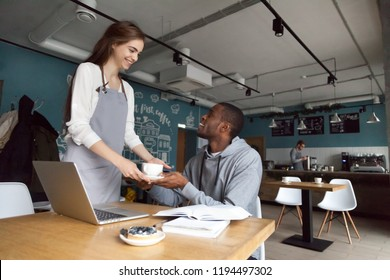 Smiling young waitress serve coffee to African American cafe visitor studying or working at table, pretty coffeehouse female worker give cappuccino or latte to black coffeeshop guest flirting with him