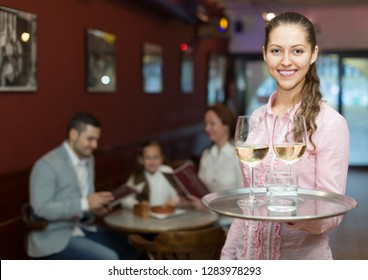 Smiling young waitress serving family of three at cafe table