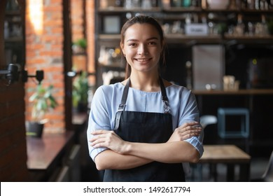 Smiling young waitress or small cafe business owner entrepreneur looking at camera, confident millennial businesswoman wear apron posing in restaurant coffeeshop interior, cafeteria worker portrait