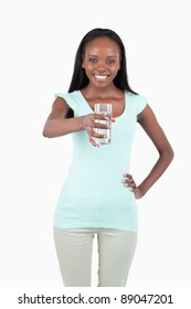 Smiling young water offering a glass of water against a white background