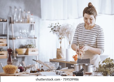 Smiling young woman adding noodles to pot while cooking in the kitchen