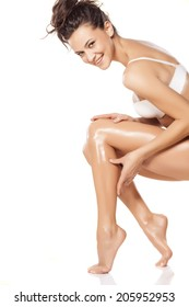 smiling young woman apply lotion on her legs