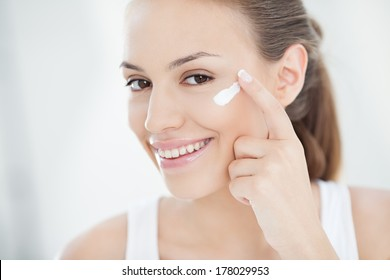 Smiling young woman applying face cream.