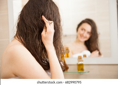 Smiling young woman applying oil mask to her hair in front of a mirror; haircare concept