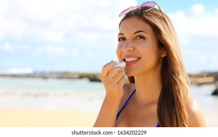 Smiling young woman applying sun protection on her lip on the beach