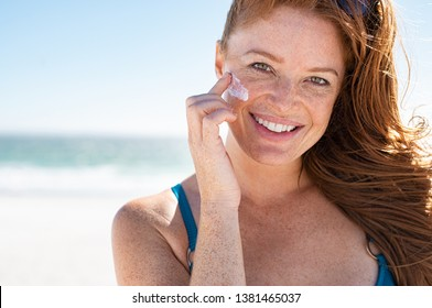 Smiling young woman applying sunscreen lotion on face at beach, with copy space. Portrait of beautiful happy girl using sunblock on her delicate skin with freckles and looking at camera.