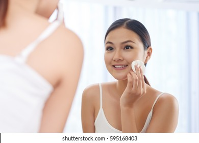 Smiling young woman applying toner on her face in front of mirror