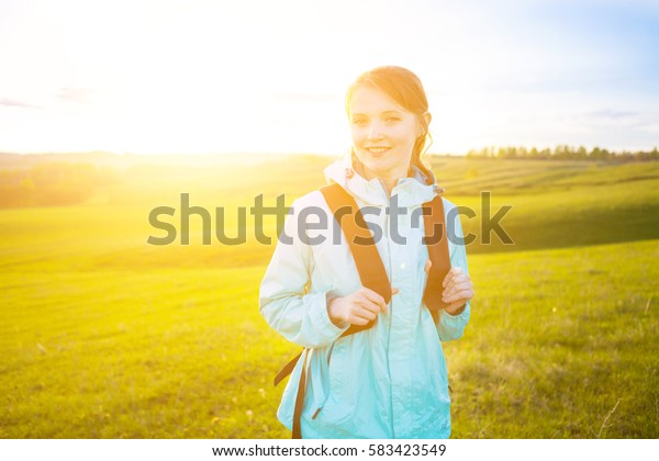 smiling young woman with backpack hiking on field