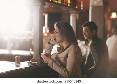 Smiling young woman at the bar drinking a coffee and having a phone call
