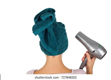 Smiling young woman with bath towel on head holding a hair dryer on isolated background - back view