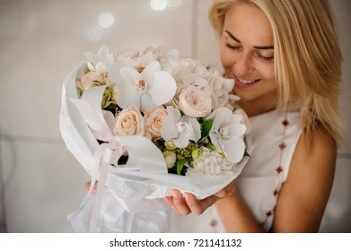 Smiling young woman with a beautiful and soft composition of flowers on a bright background
