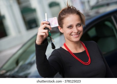 Smiling young woman behind the car showing her driver's license and keys