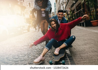 Smiling young woman being pushed on skateboard by her boyfriend outdoors on street, with friends piggybacking in background on the street. Group of friends enjoying themselves outdoors on city street.