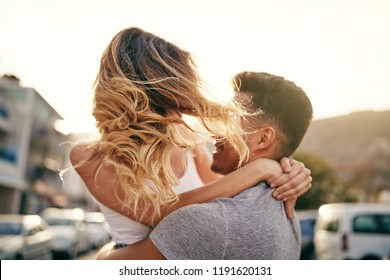 Smiling young woman being twirled in the air by her boyfriend while sharing a fun moment together in the city