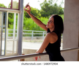 smiling young woman in black dress taking a portrait picture with her smarthphone