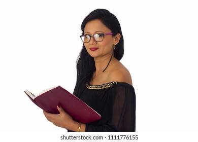 Smiling young woman in black salwar suit holding a book. Side pose