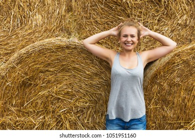 A smiling young woman with blond hair stands on the background of haymaking.