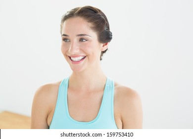 Smiling young woman in blue sports bra looking away