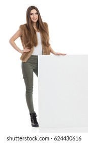 Smiling young woman in brown fur waistcoat, khaki pants and black boots is standing partially behind blank placard and looking at camera. Front view. Full length studio shot isolated on white.