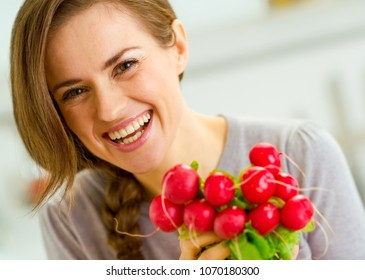 smiling young woman with bunch of radishes