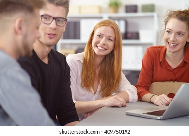 Smiling young woman in a business meeting with two male and a female colleague watching the men with an interested expression as they talk
