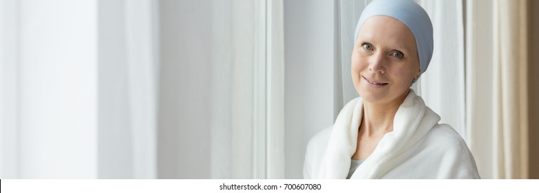Smiling young woman with cancer standing by the window