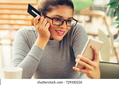 Smiling young woman with card keeping video blog