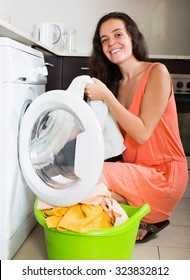 Smiling  young woman cheking white clothes near washing machine  at home