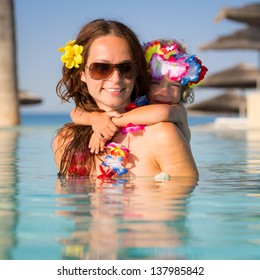 Smiling young woman with child playing in swimming pool. Summer vacations concept