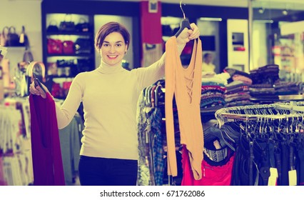 Smiling young woman choosing colorful blouse in womens cloths shop