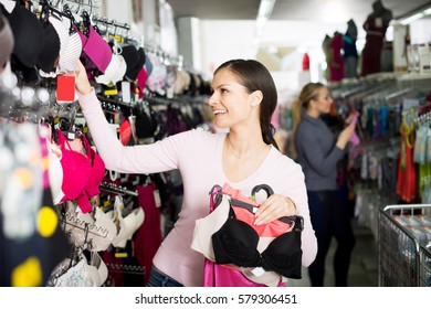 Smiling young woman choosing sexy silky bra in lingerie shop
