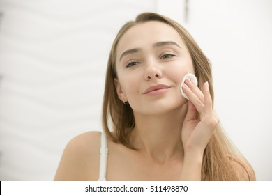 Smiling young woman cleaning her skin with a cotton pad, looking at the mirror at home bathroom. Beauty, skin care concept, lifestyle