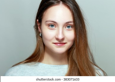 smiling young woman close-up face portrait without make-up with messy hair isolated on white background