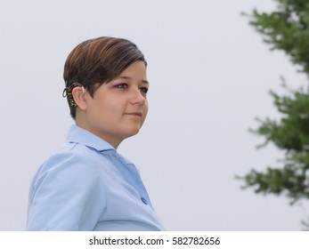 Smiling Young Woman With Cochlear Implant - Photograph of a deaf,  Russian born, American adopted young woman wearing her janitorial work uniform.  Selective focus on facial features.