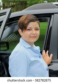 Smiling Young Woman With Cochlear Implant - Photograph of a deaf,  Russian born, American adopted young woman wearing her janitorial work uniform, preparing to drive to work.