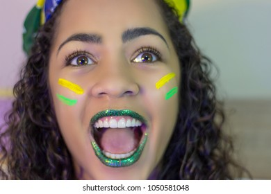 A smiling young woman with the colors of flag of the Brazil painted on her face.