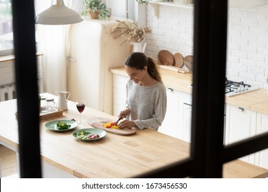 Smiling young woman cutting fresh vegetables on wooden board, cooking salad and drinking red wine, standing in modern kitchen, happy female preparing for romantic date or festive dinner top view