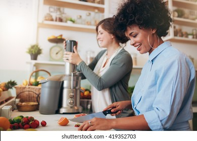 Smiling young woman cutting fruits with coworker using juicer in background, two women preparing fruit juice at cafe counter.