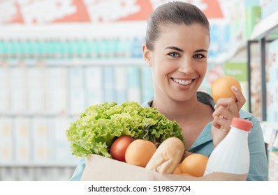 Smiling young woman doing grocery shopping at the supermarket, she is holding a bag with fresh vegetables, bread and milk
