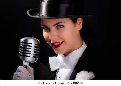 Smiling young woman dressed in vintage top hat & tails, poses next to an old style microphone.