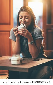 Smiling young woman is drinking coffee with whipped cream while sitting in the cafe