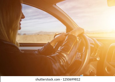Smiling young woman driving a car. Light effect, toned image