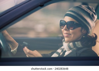 Smiling young woman driving a car and using mobile phone