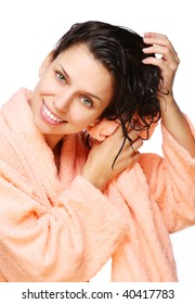 Smiling young woman drying hair with towel in a bathrobe  on a white background