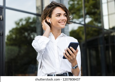 Smiling young woman in earphones standing outdoors at the street, talking on mobile phone